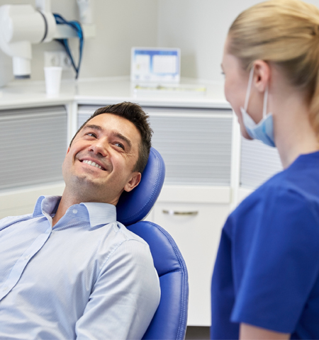 Man and Dental Hygienist Laughing in Raleigh, NC